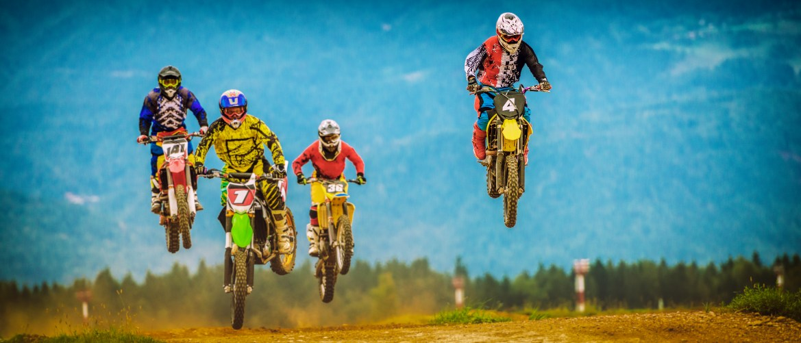 Four motocross racers in mid-air during a jump on a race track.