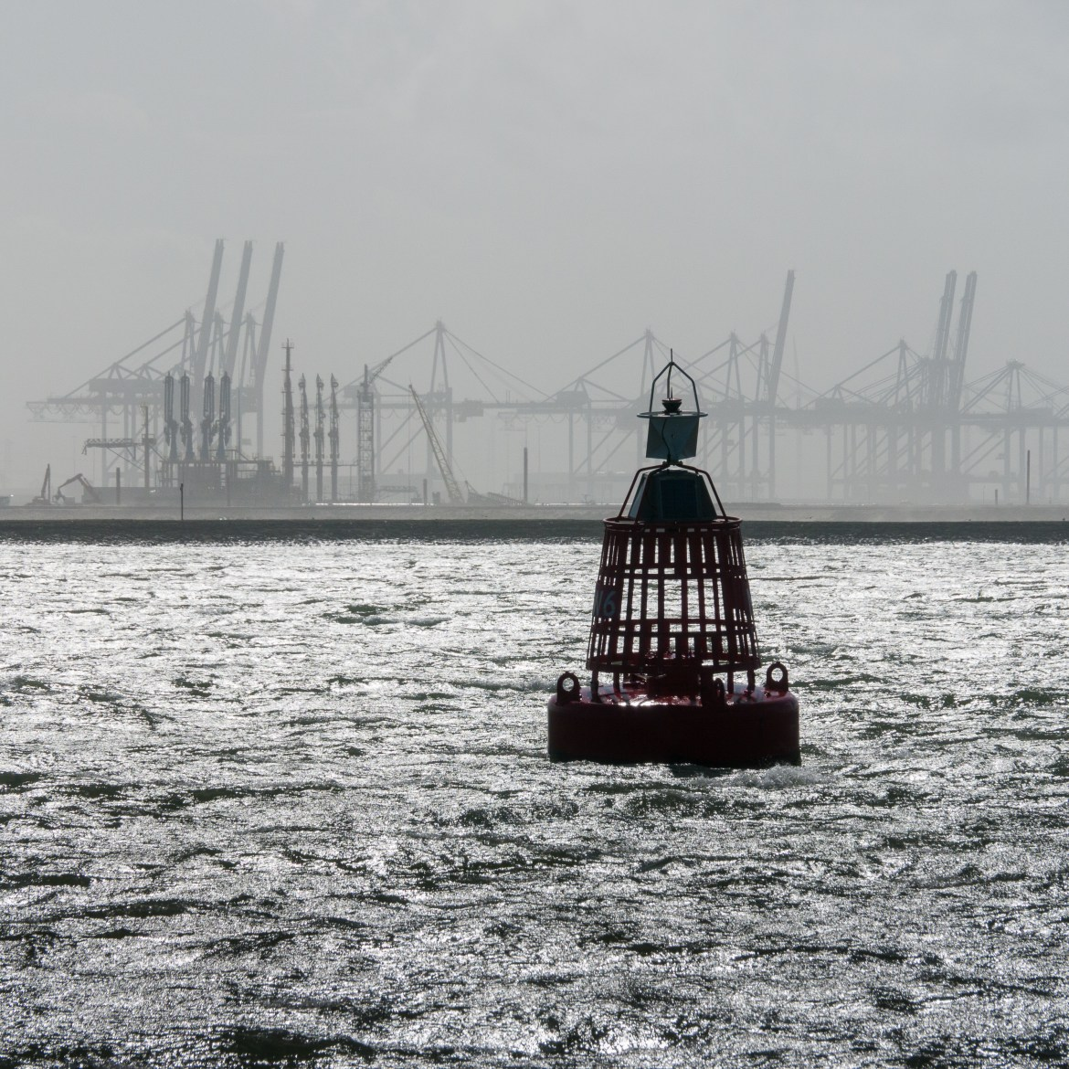 a buoy in Rotterdam Harbor with an empty industrial facility in the background