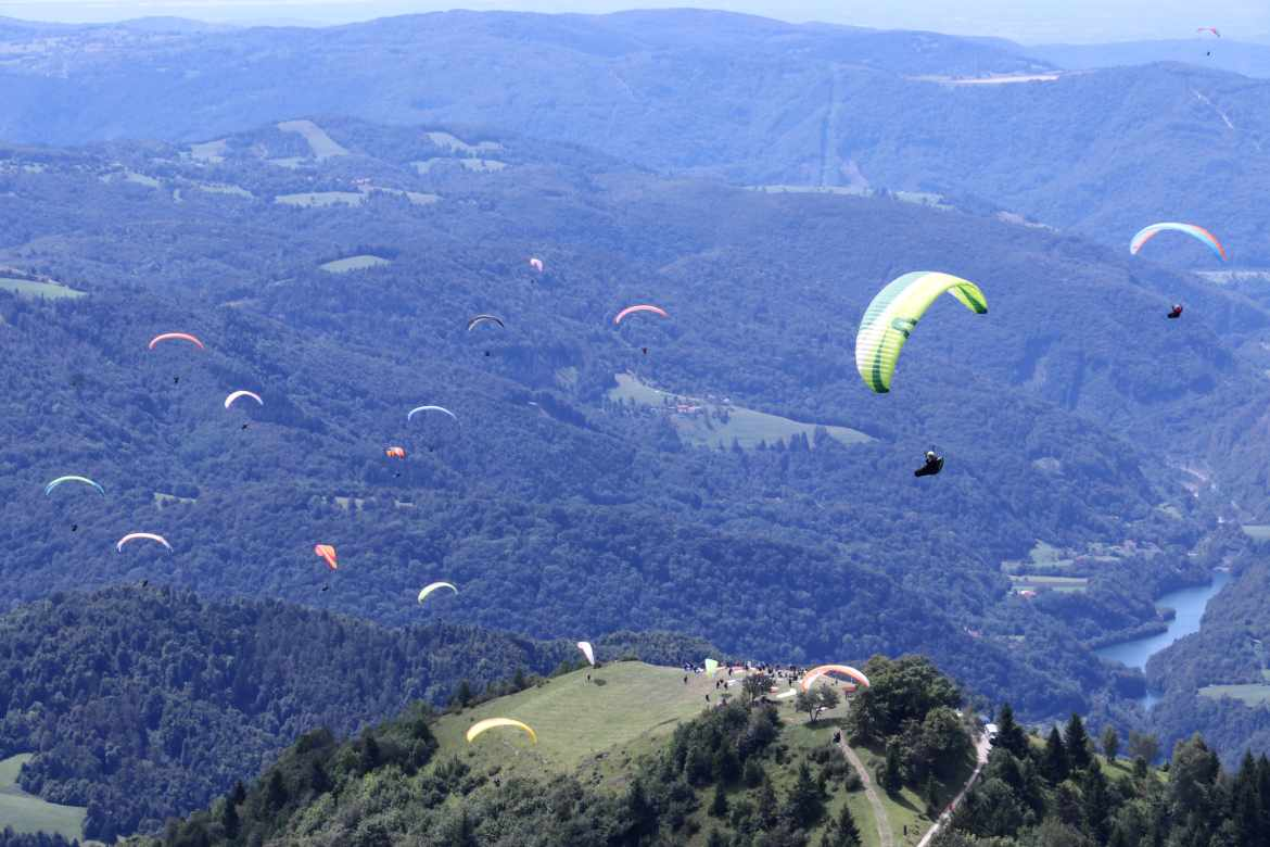 group of people paragliding over the countryside
