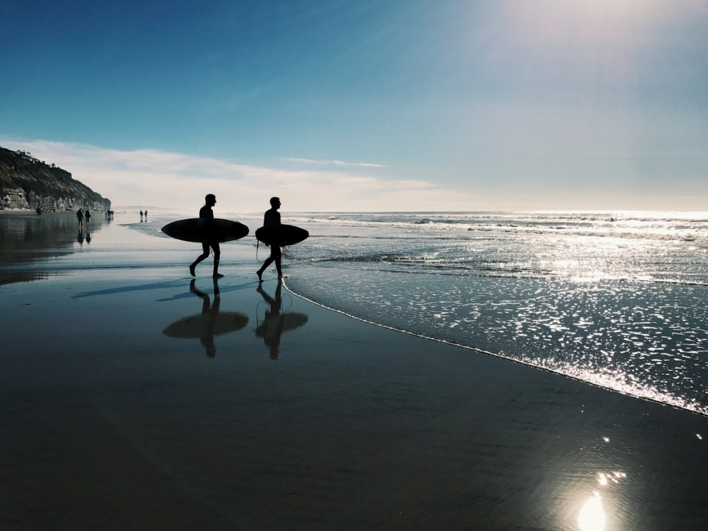 two surfers walking on a clean beach in San Diego