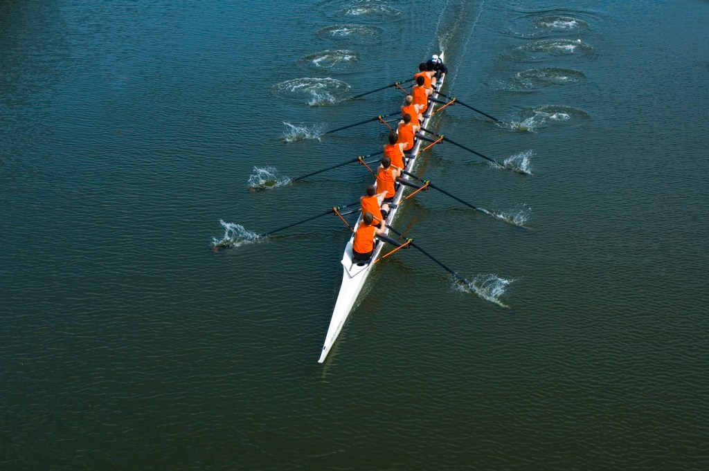 team of rowers working together to move their boat forward