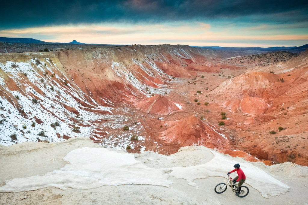 man pausing on a bike in the desert in winter