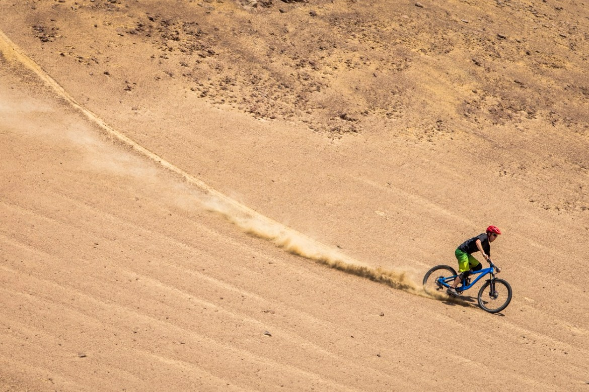 man biking downhill in the desert to indicate the downward trend of gas prices