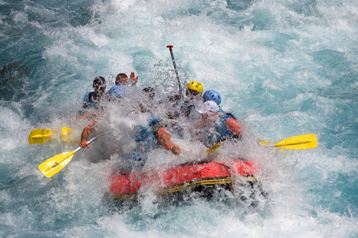 Group of white water rafters in churning water