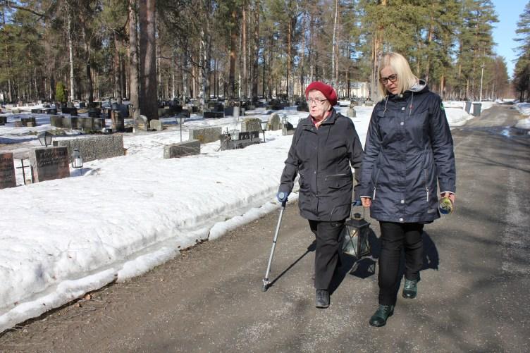 Virpi Kiviniemi ja Ella Eronen kävelevät Joensuun hautausmaalla.