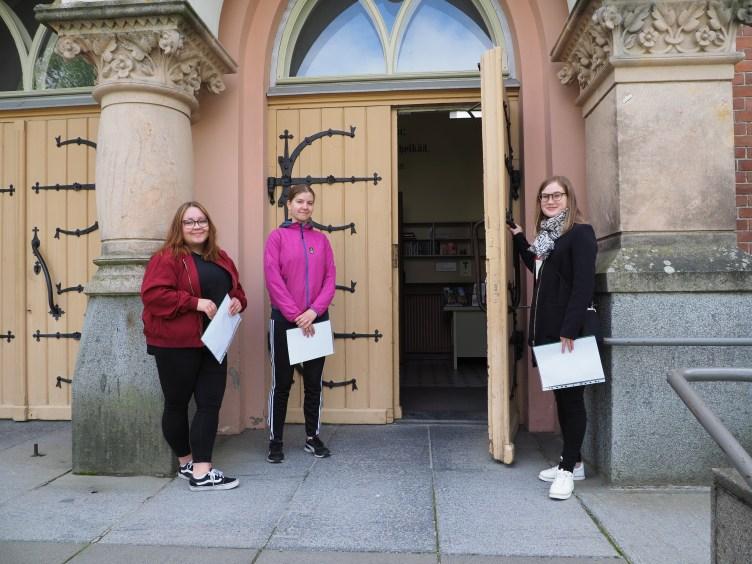 Kirkon oppaat Niina Muikku, Vilina Tarnanen ja Suvi Hakkarainen Joensuun kirkon ovella.