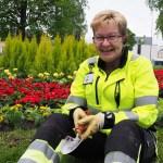 Pirjo Auvinen istuu Pohjoisen rantapuiston kukkapenkin edustalla.