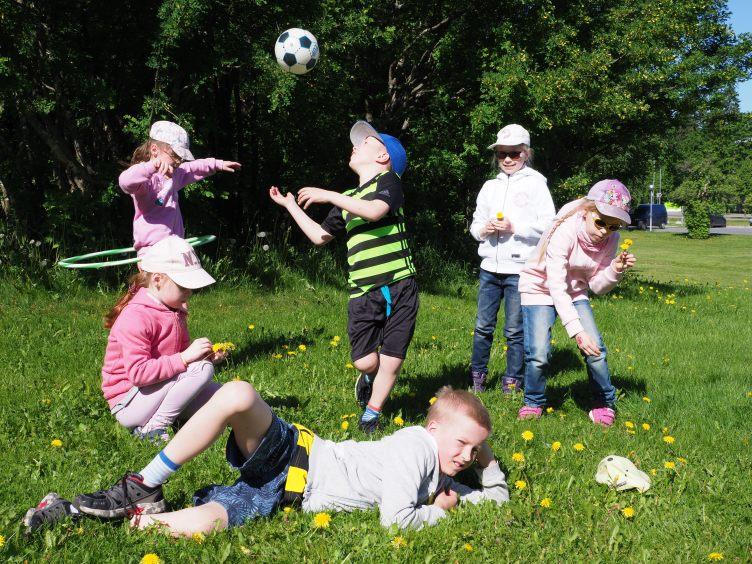Kerholaiset leikkivät nurmikolla.