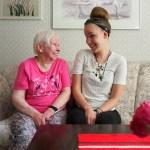 88-vuotias Rauha Torniainen ja 22-vuotias Veera Kettunen istuvat Torniaisen kotisohvalla ja katsovat nauraen toisiaan.