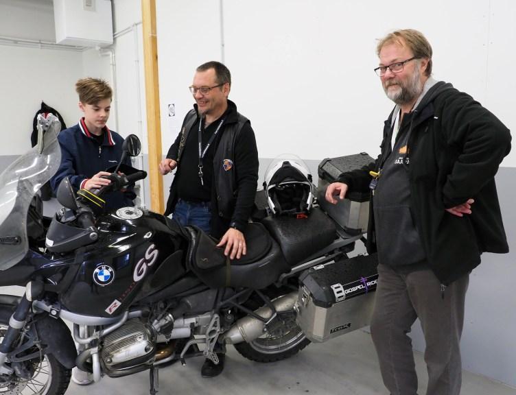 Moottoripajaan tutustumassa käynyt Leo Kirves, pajan vapaaehtoinen ohjaaja Timo Sund ja erityisnuorisotyönohjaaja seisovat Timo Sundin moottoripyörän ympärillä.