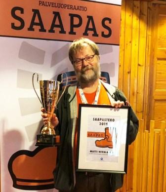 Matti Nevalainen seisoo palkintopolaali kädessään.