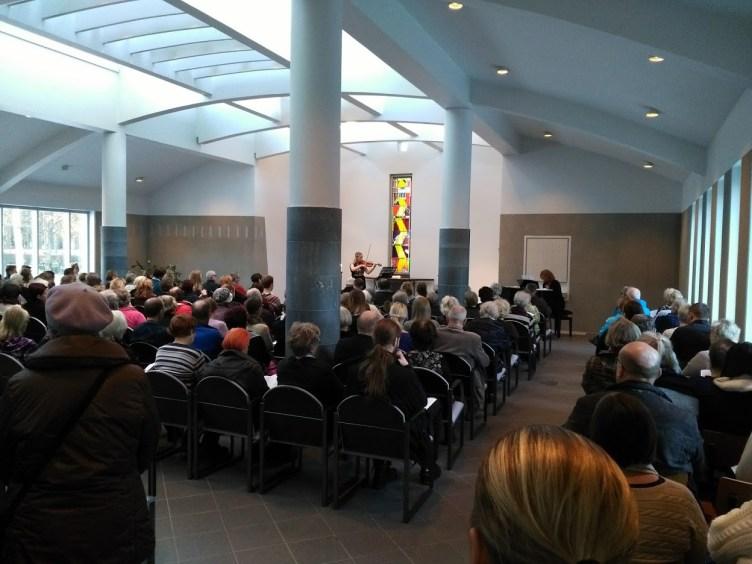 Yleisö istuu Ristinkappelin penkeillä. Nainen soittaa viulua yleisön edessä.