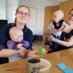Äidit istuvat pöydän ääressä vauvat sylissään.