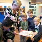 Nuorisotyönohjaaja Noora Kähkönen pitää kädessään Kato mua -tapahtuman julistetta. Viisi alakouluikäistä poikaa ovat kokoontuneet katsomaan julistetta.