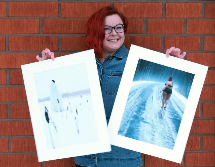 Kuvataitelija Satu Laaninen seisoo tiiliseinän edessä ja pitää käsissään kahta valokuvateostaan. Valokuvateoksissa on naishahmot talvisessa maisemassa.