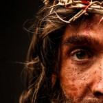 Osa orjantappurakruunua kantavan Kristuksen kasvoista. Kristus katsoo suoraan kameraan vakavana, kasvoilla on verta ja likaa.