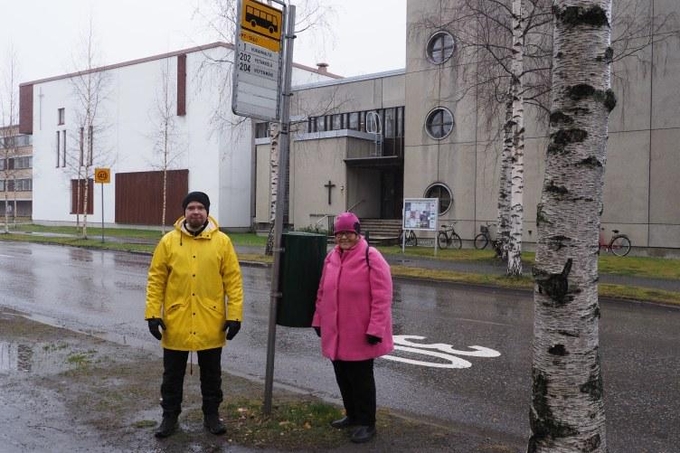 Mies ja nainen seisovat bussipysäkillä.