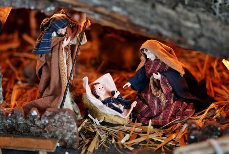 Kuvassa seimiasetelma, jossa Joosef, Jeesus-lapsi ja Maria tallin olkisella lattialla. Jeesus-lapsi makaa seiemssä, Maria on kumartunut hänen puoleensa ja Joosef seisoo turvallisena hahmona seimen toisella puolella.