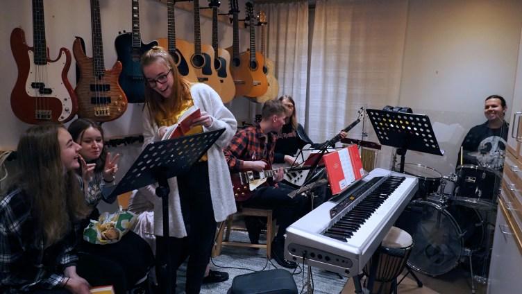 Iloinen nuorten joukko Rantakylän kirkon bändikämpässä. Kämpän seiniällä on kitaroita ja bassoja, nuoret ovat ryhmittyneet erilaisten soitinten taakse, etualalla tyttöjoukko juttelee keskenään selaten Nuorten seurakunnan veisut -kirjaa.