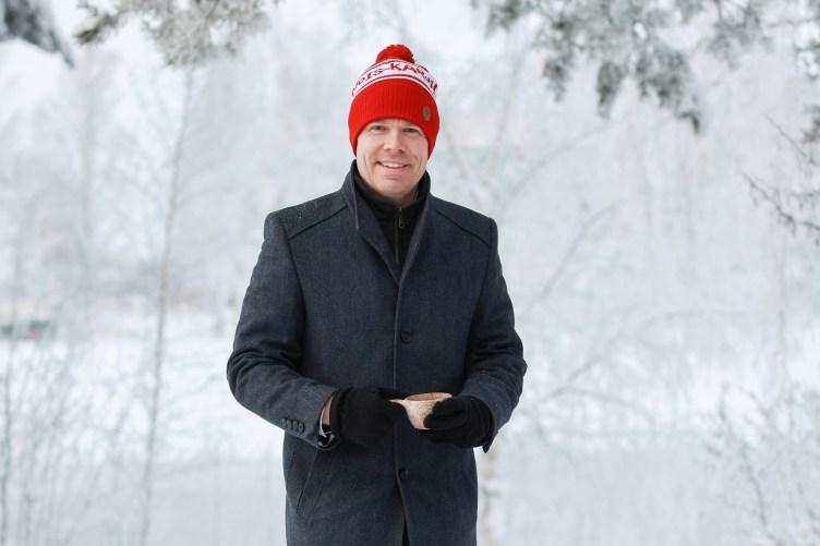 Maakuntajohtaja Markus Hirvonen seisoo lumisessa maisemassa kuksa kädessään ja katsoo hymyillen kameraan.