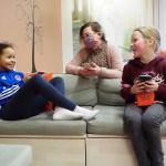 Kaksi alakouluikäistä tyttöä istuu iltapäiväkerhon sohvassa kännykät kädessään ja katsovat iloisina toisiaan. Lapsiasiahenkilö Noora Kähkönen nojaa sohvan takana sohvan selkänojaan tyttöjen keskellä ja juttele heidän kanssaan.