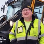 Auramies Pekka Kontu seisoo työvaatteissa Wille-lumitraktorinsa edessä ja katsoo hymyillen kameraan.
