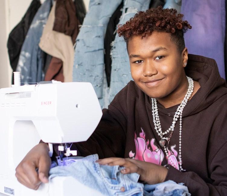 Nuori poika istuu ompelukoneen ääressä ompelemassa farkkukankaista vaatetta, taustalla paljon kankaita ja farkkuja.