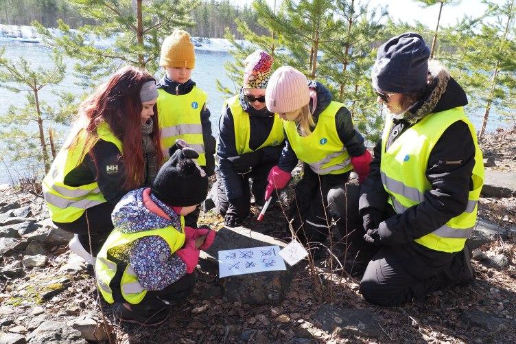 Keltaisiin huomioliiveihin pukeutuneet lapset ja ohjaajat kyykistyneenä yhdessä tutkimaan paperia.
