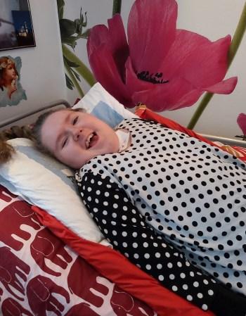Kolarissa vammautunut Kirsi Leskelän tytär Marika makaa sängyllä ja katsoo iloisesti nauraen kameraan.