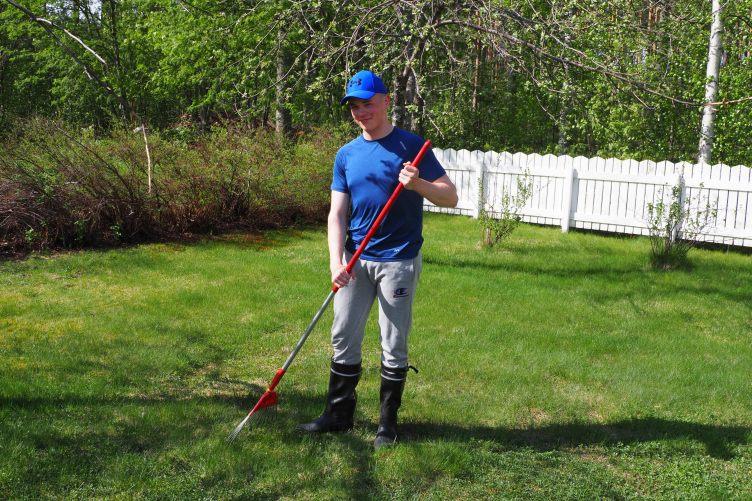 Sinipaitainen poika haravoi nurmikkoa ja katsoo hymyillen kameraa.