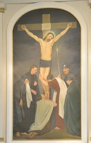 Kuva Enon kirkon alttaritaulusta. Taulussa Jeesus ristillä, ristin juuressa kuusi henkilöä.