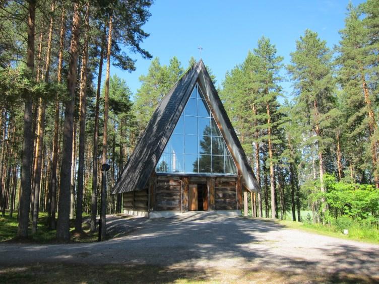 Puinen kirkko isolla lasi ikkunalla, taustalla metsää.