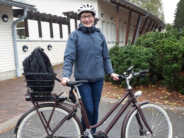 Lea Vuojolainen poseeraa sähköpyörän kanssa Pyhäselän seurakuntatalon edessä.