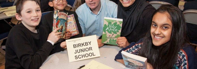 World Book Day Quiz compare and children's poet Gez Walsh sat at a table with Birkby Junior's winning quiz team: Ansah Sabir, Alisha Amjad, Nabil Hamdun and Dominic Beaumont