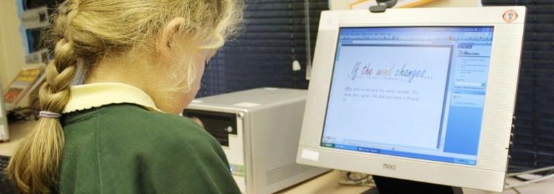 school girl working at desktop computer