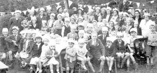 An old black and white picture that show a group of children and women around a table with big smile, with bunting hanging in the background.