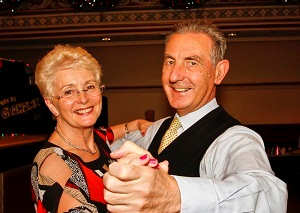 A glamorous dressed smartly couple in a dance move facing the camera. Both have big smiles