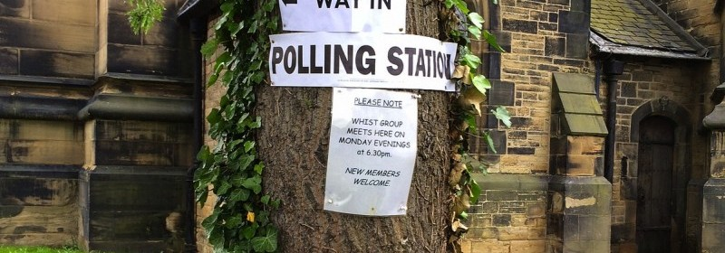 polling station sign pinned to tree