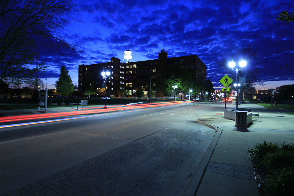Cars zoom by leaving a trail of lights past Water Tower Place in Cedar Rapids, IA by Kirk Taylor