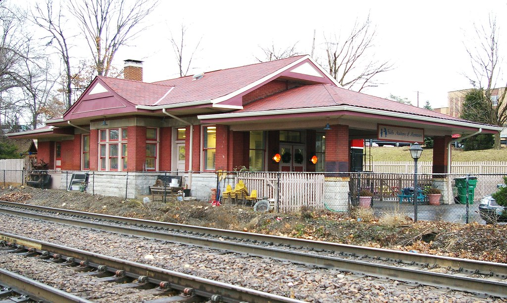 A small red brick and stonebuilding sits next to the train tracks