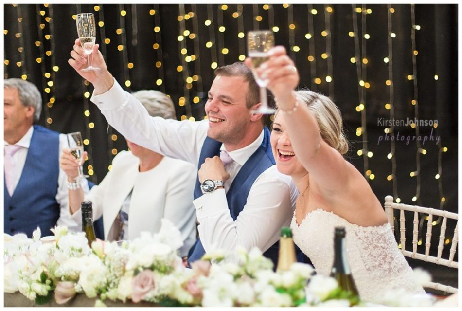 bride and groom lifting glasses to toast