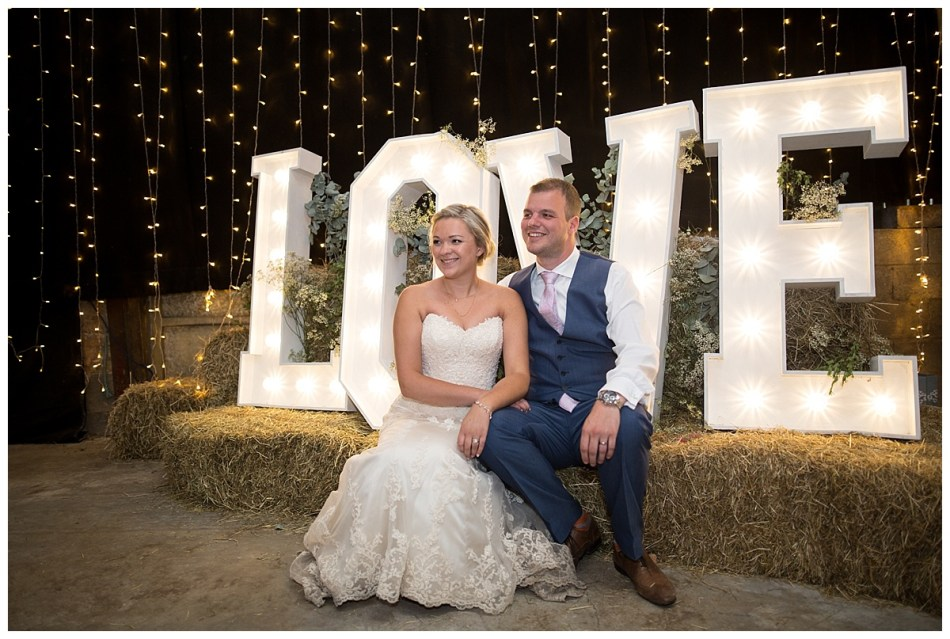 bride and groom sitting by love sign