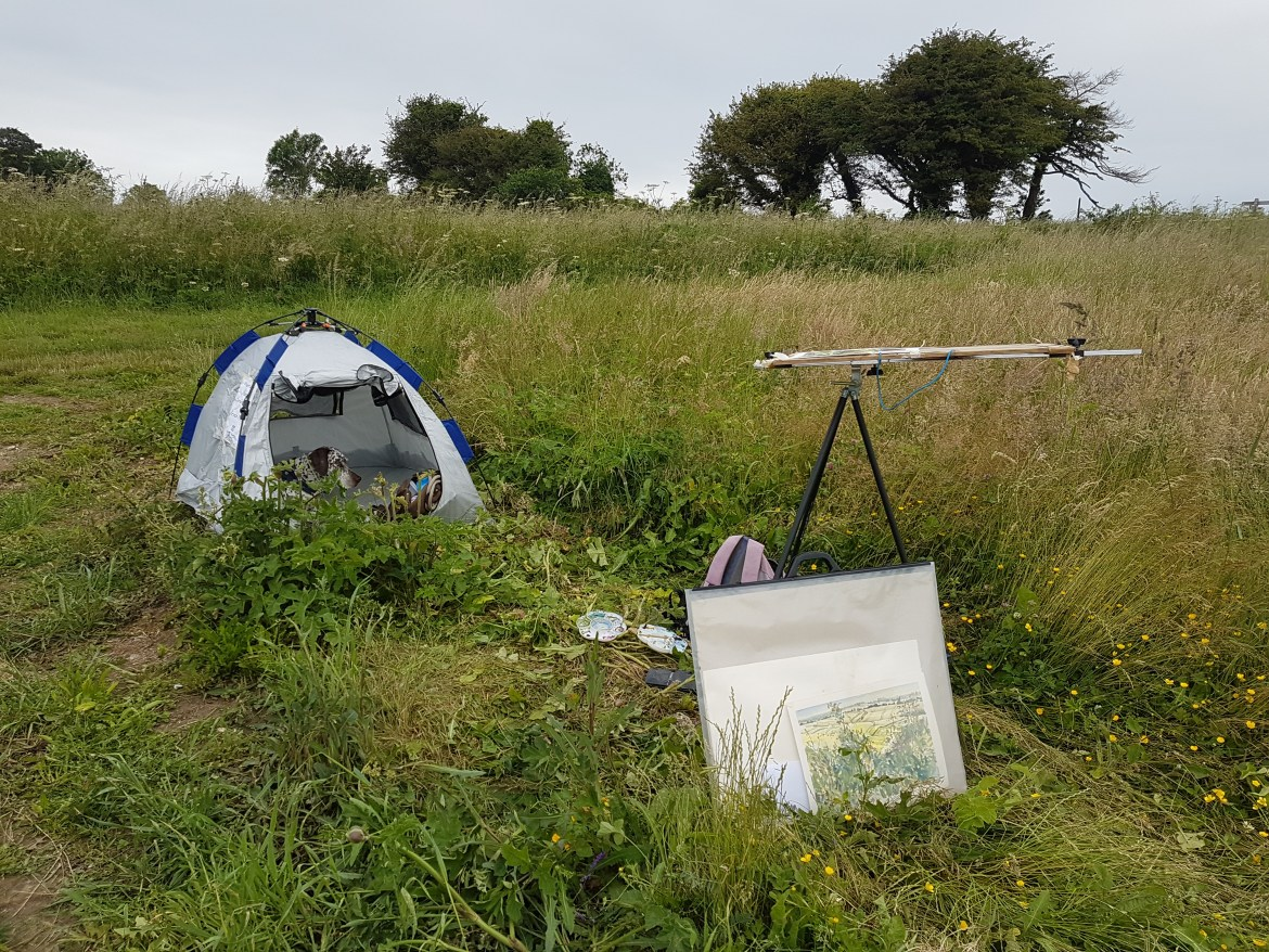 dog tent, easel and paintings in a meadow