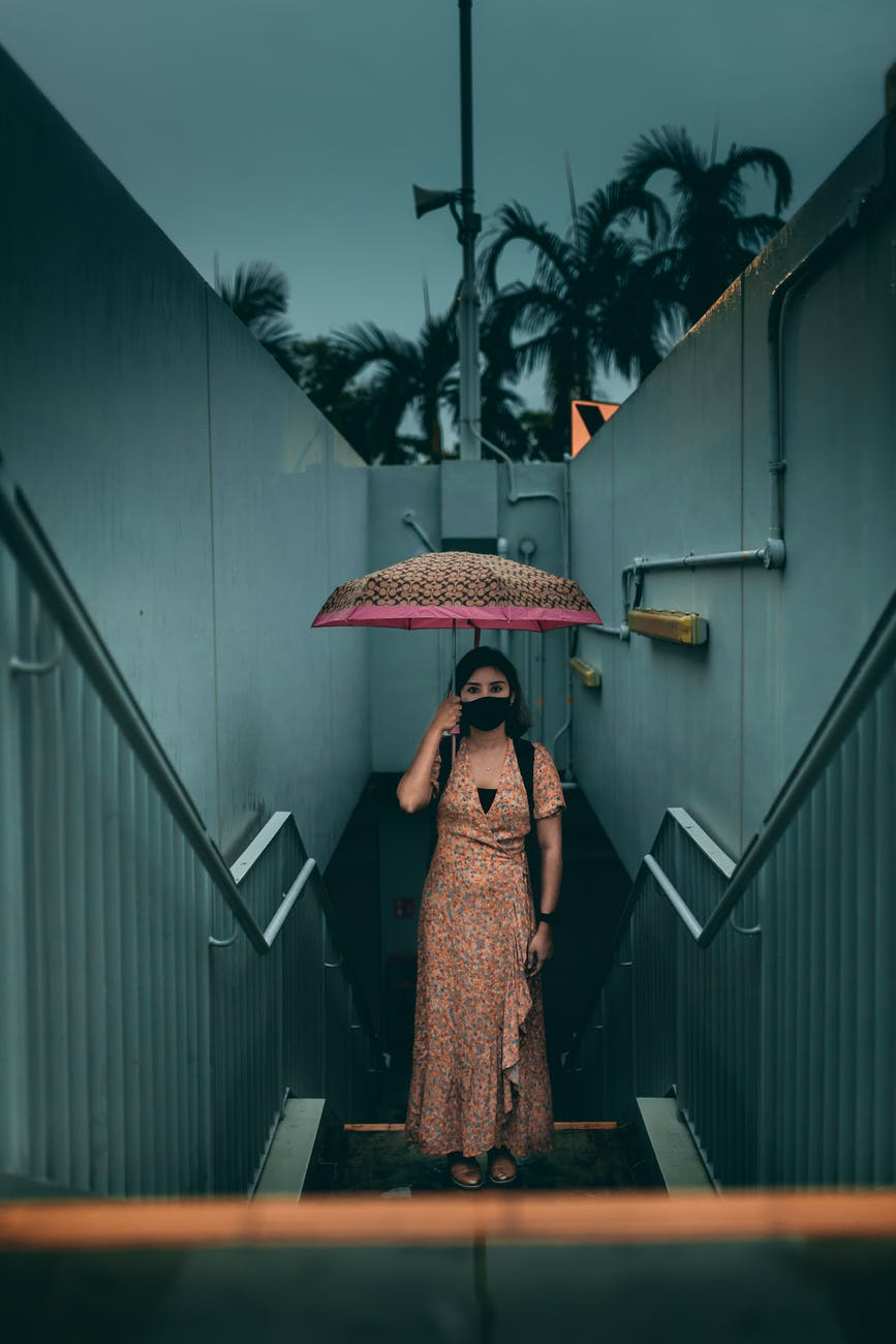 woman in face mask under umbrella standing on street steps