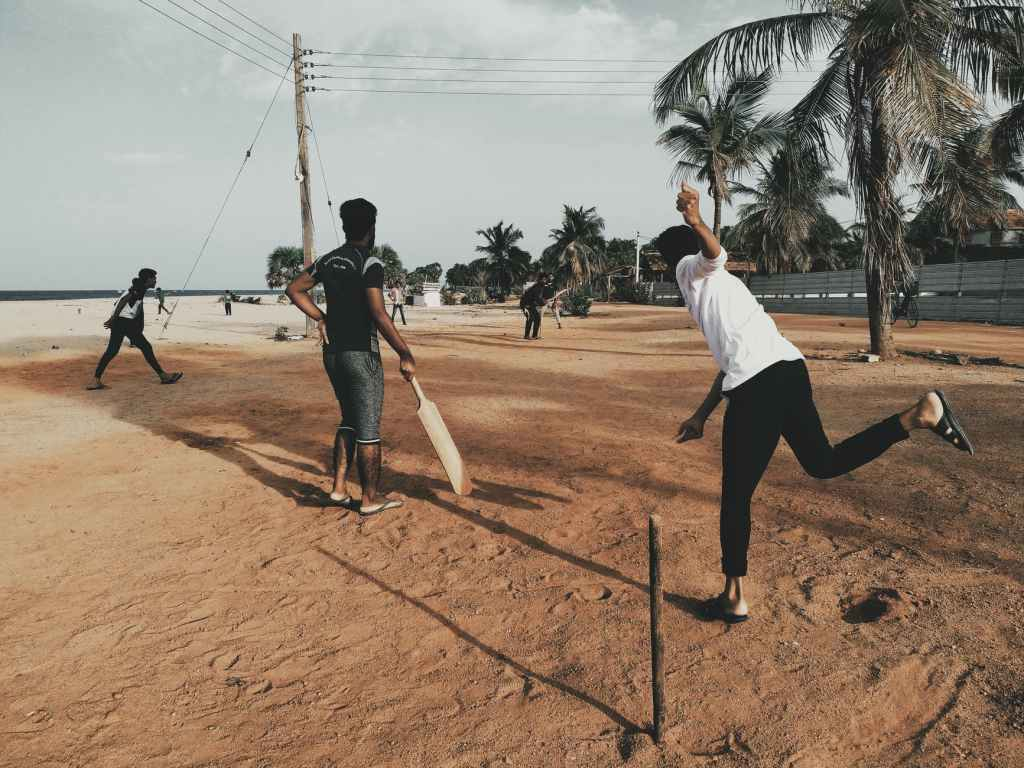 men playing cricket at beach