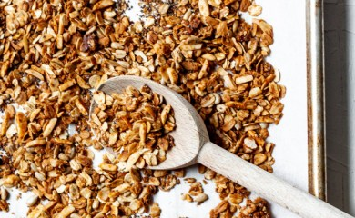 crunchy granola on a sheet pan with a spoon scooping it our