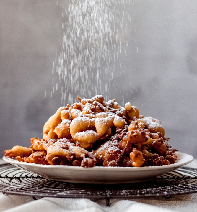 A plate of funnel cake bites on a wire rack with powdered sugar being sprinkled over