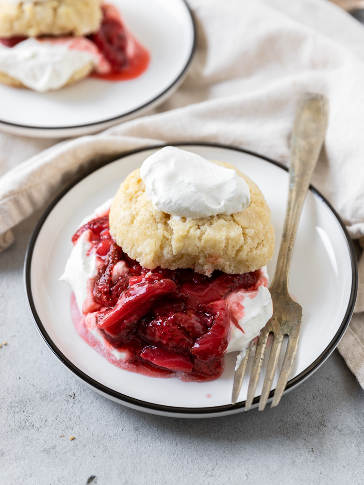 A strawberry shortcake topped with a dollop of fresh whipped cream