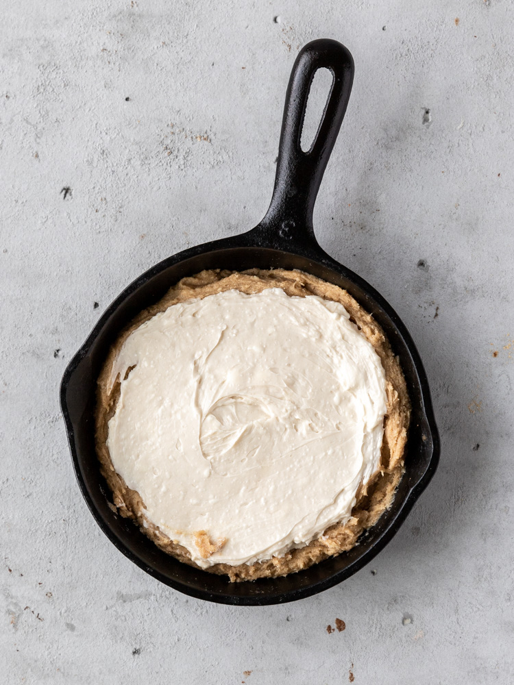 Half of the cookie dough pressed into the skillet with the cheesecake filling spread on top