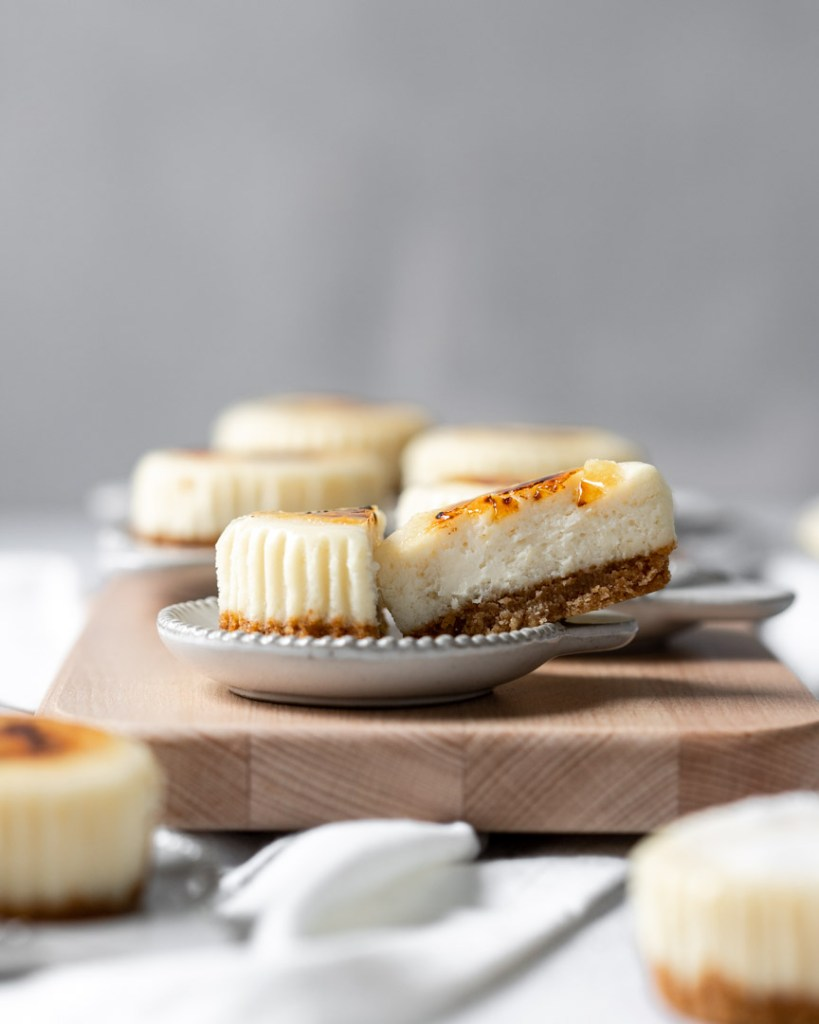 A straight on shot of a creme brûlée cheesecake that is cut in half